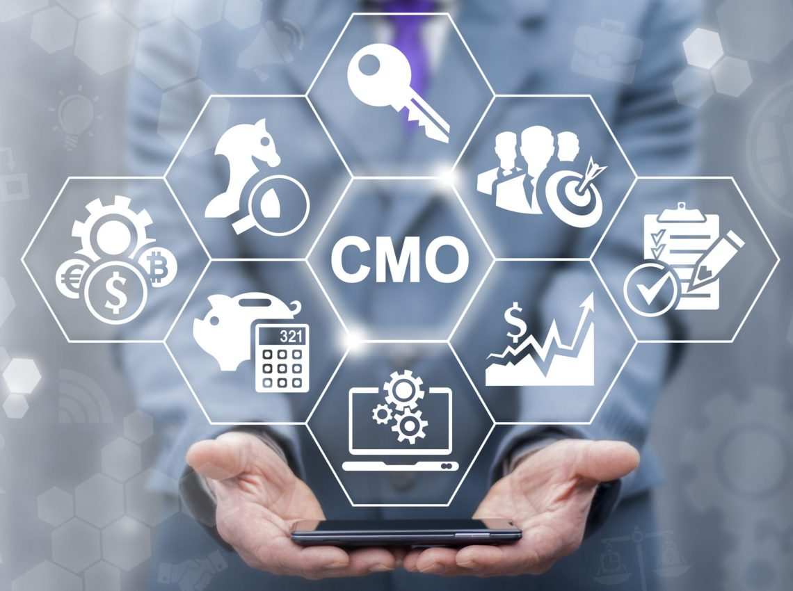 CMO - Chief Marketing Officer business shopping web store concept. Leadership internet shop mobile tech, finance, strategy office work. Businessman keep smart phone with cmo icon on virtual screen
